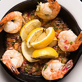 Shrimp and lemons over salsa in sautee pan